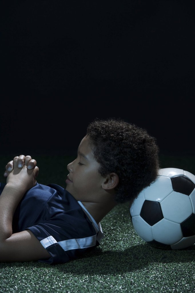 Stock Photo: 1439R-1005422 Boy sleeping with football as pillow