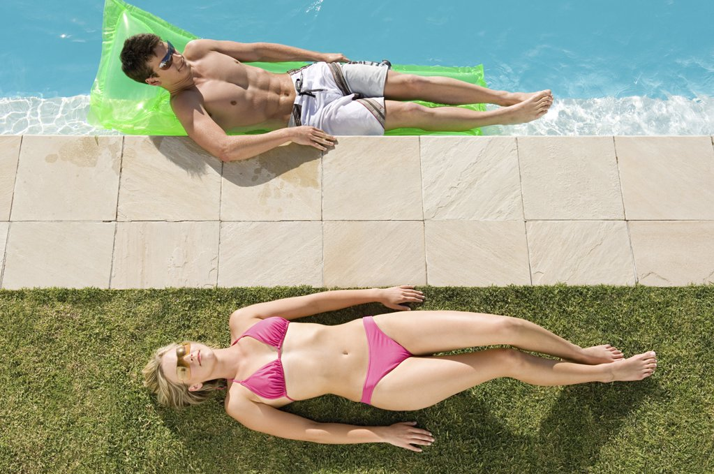 Stock Photo: 1439R-1005520 Couple sunbathing at the pool