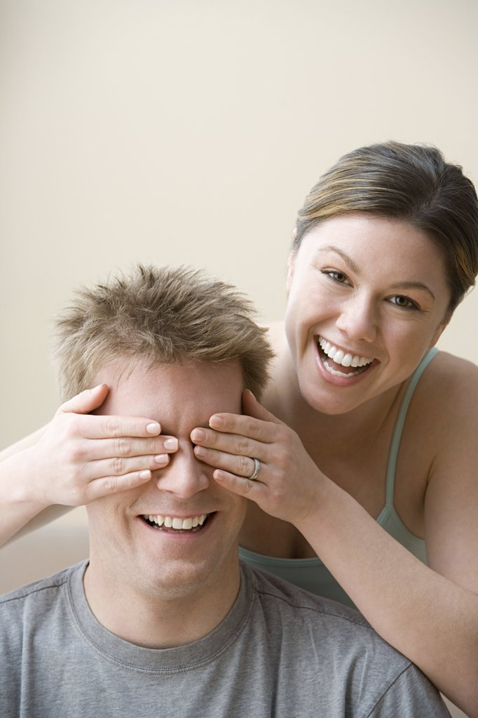 Woman covering husband's eyes : Stock Photo
