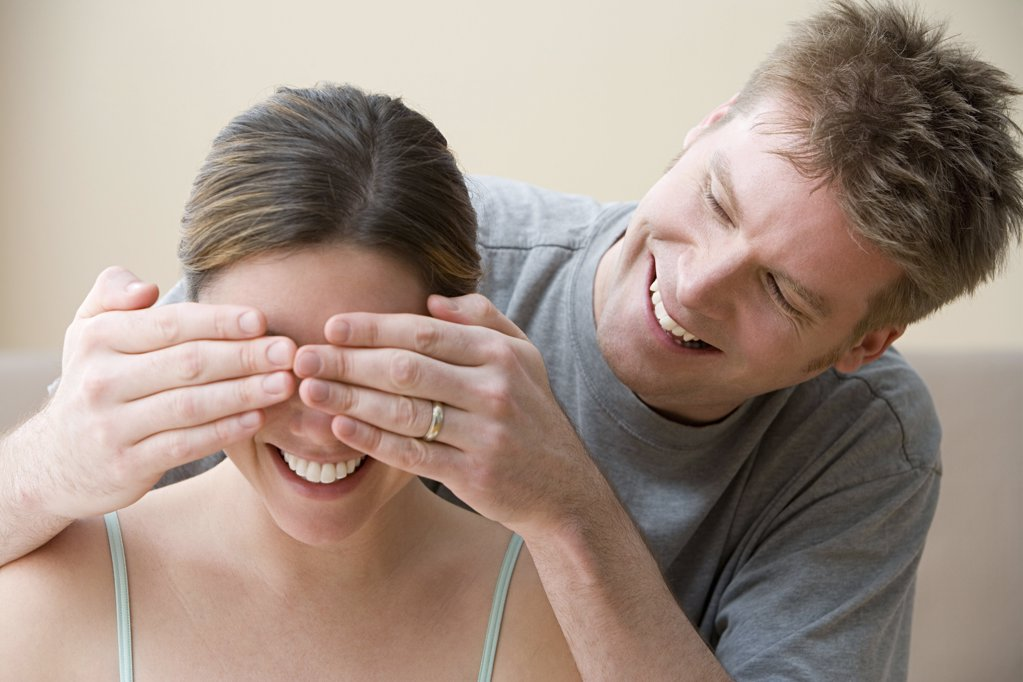 Man covering wife's eyes : Stock Photo