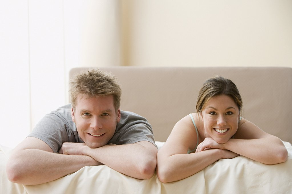 Stock Photo: 1439R-1005724 Couple lying on bed