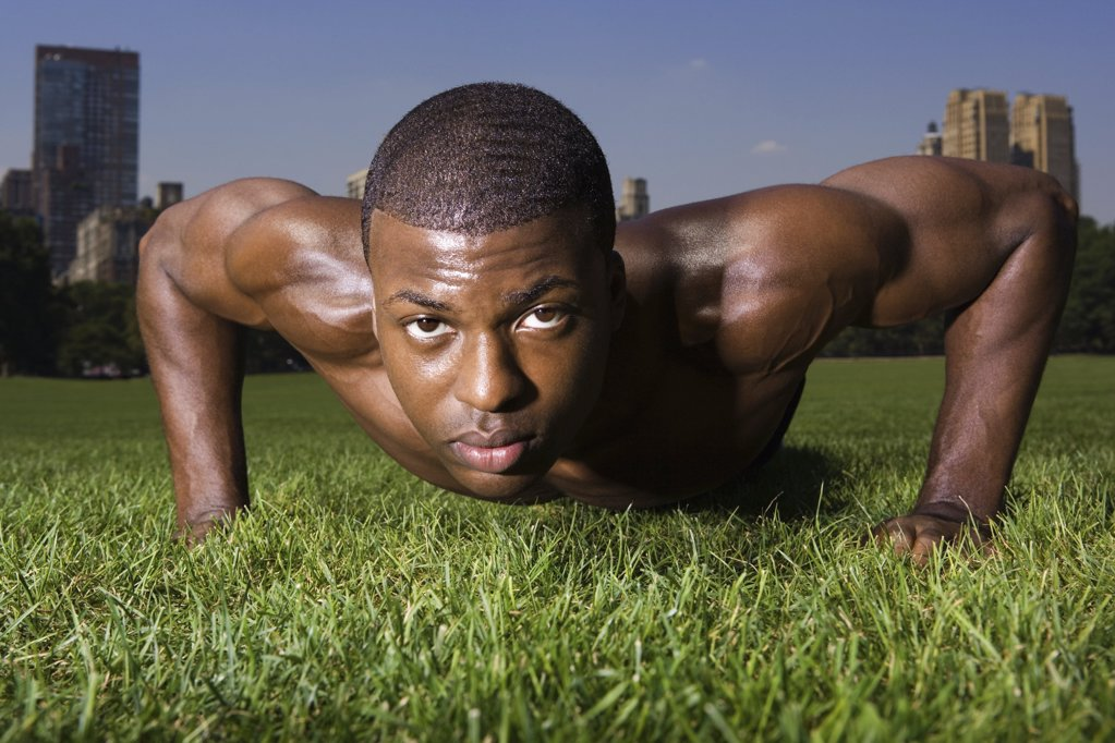 Man doing press ups in the park : Stock Photo