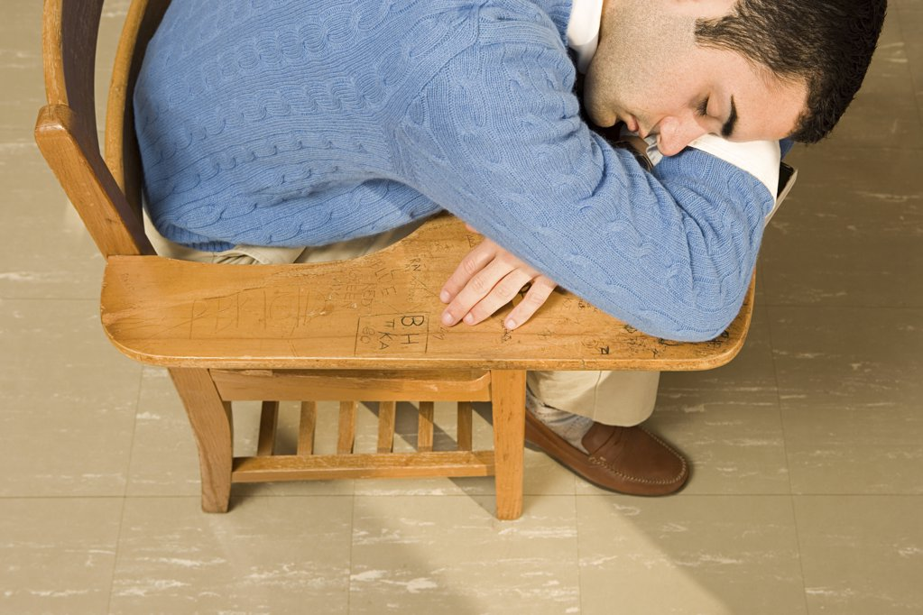 Stock Photo: 1439R-1007136 Male student sleeping in a lesson