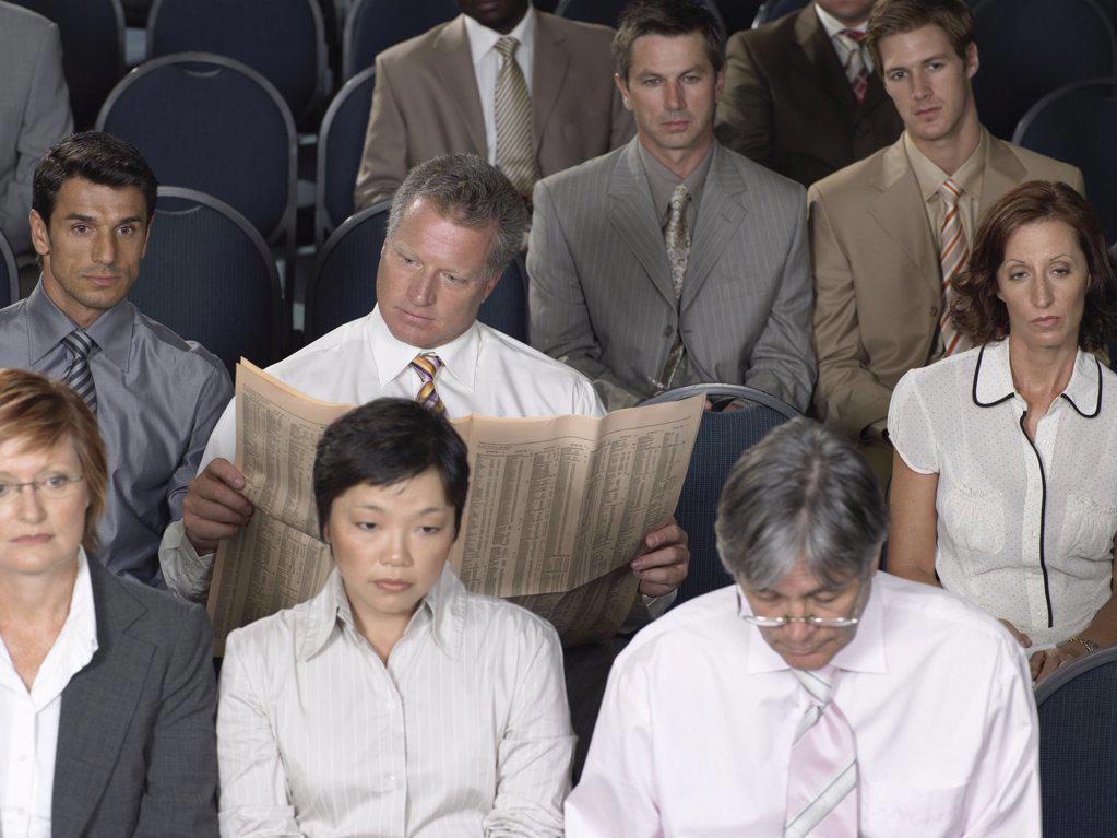 Stock Photo: 1439R-1007592 Businessman reading during presentation