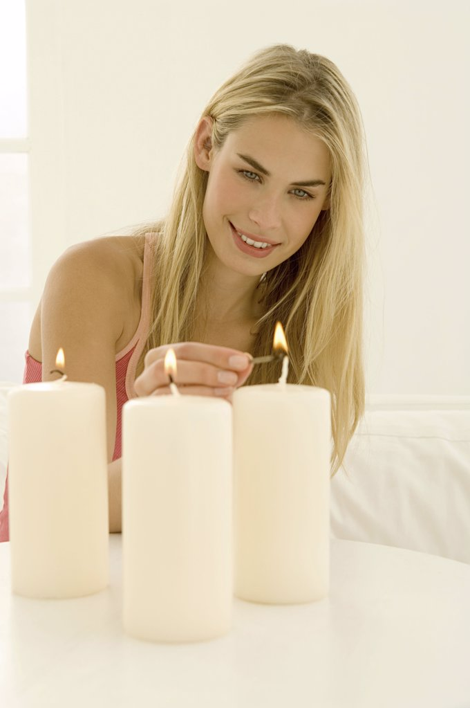 Woman lighting three candles : Stock Photo
