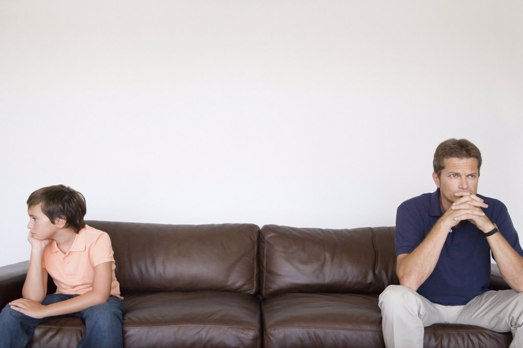 Father and son at opposite ends of sofa : Stock Photo