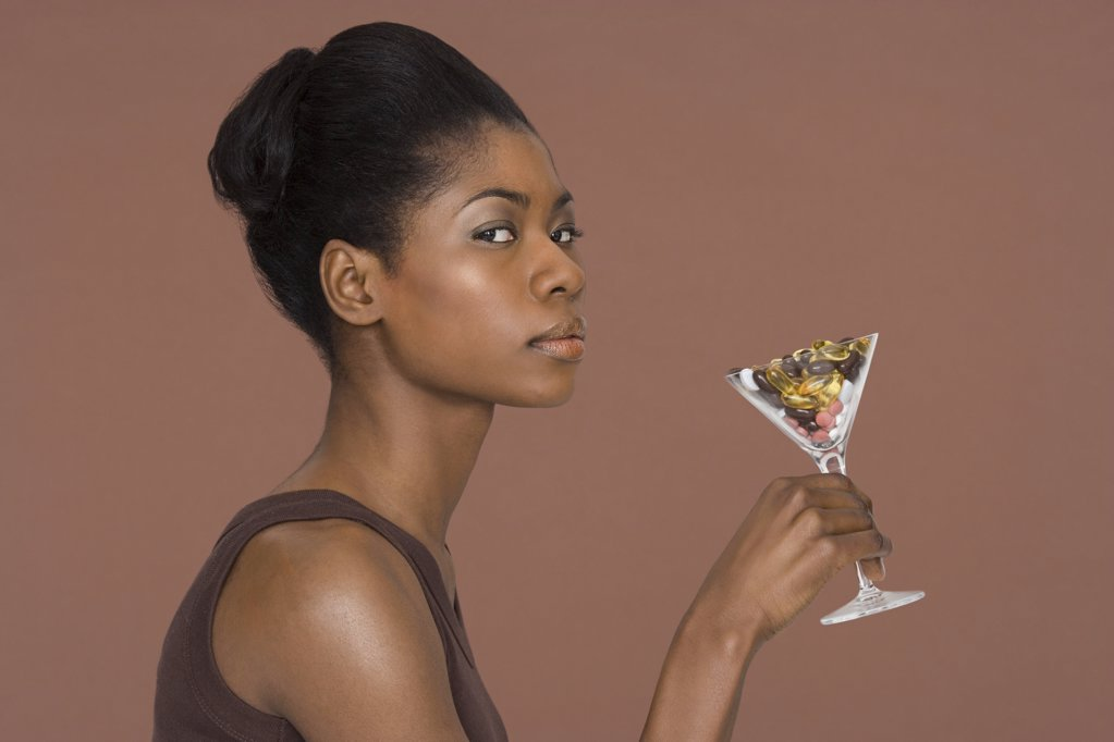 Young woman holding a cocktail glass full of vitamins : Stock Photo