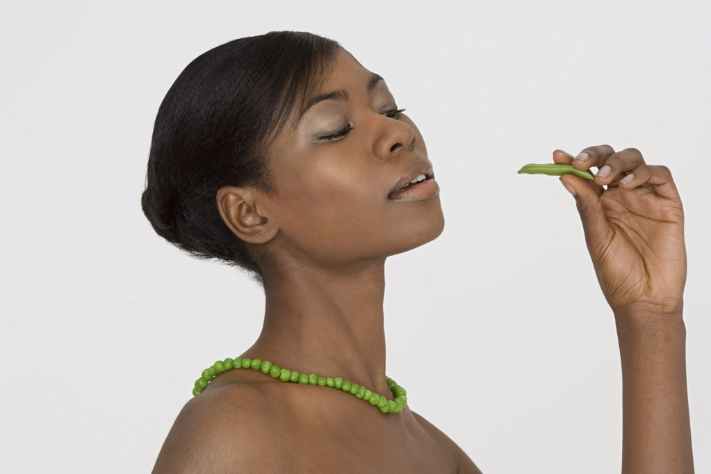 Young woman wearing a pea necklace : Stock Photo