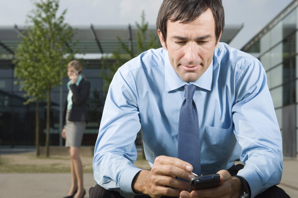 Man using handheld computer outdoors : Stock Photo