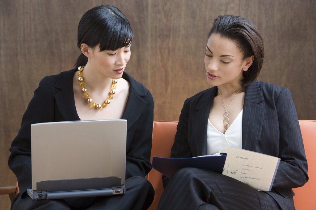 Two young women working with laptop : Stock Photo