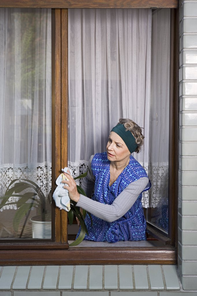 Woman dusting window frames : Stock Photo