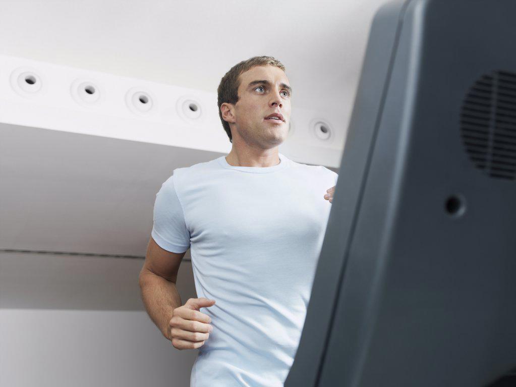 Man on treadmill in health club  : Stock Photo