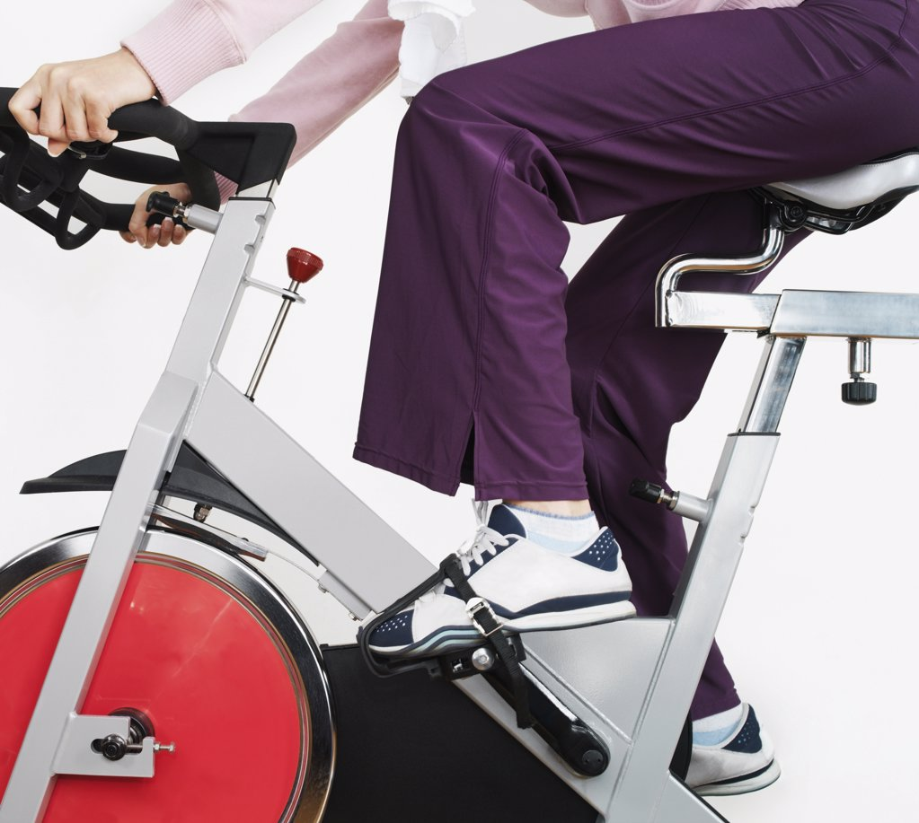 Woman on exercise bike in health club  : Stock Photo