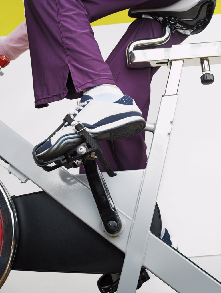 Stock Photo: 1439R-1015745 Woman on exercise bike in health club