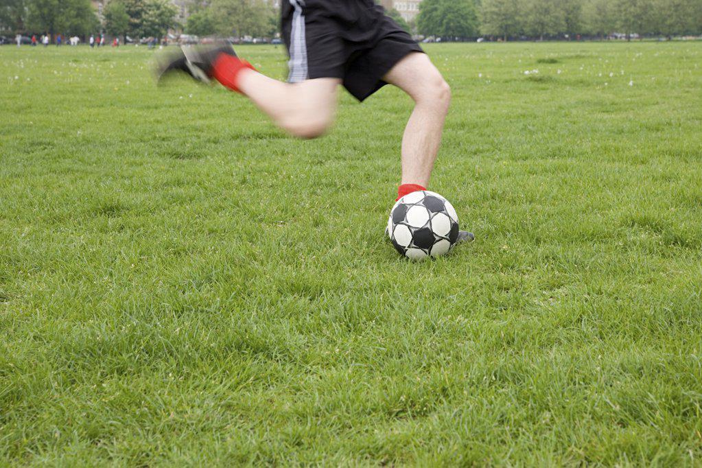 Footballer kicking ball : Stock Photo