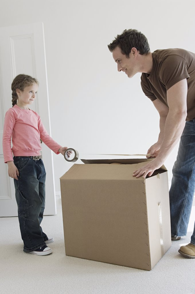 Father and daughter taping up box : Stock Photo