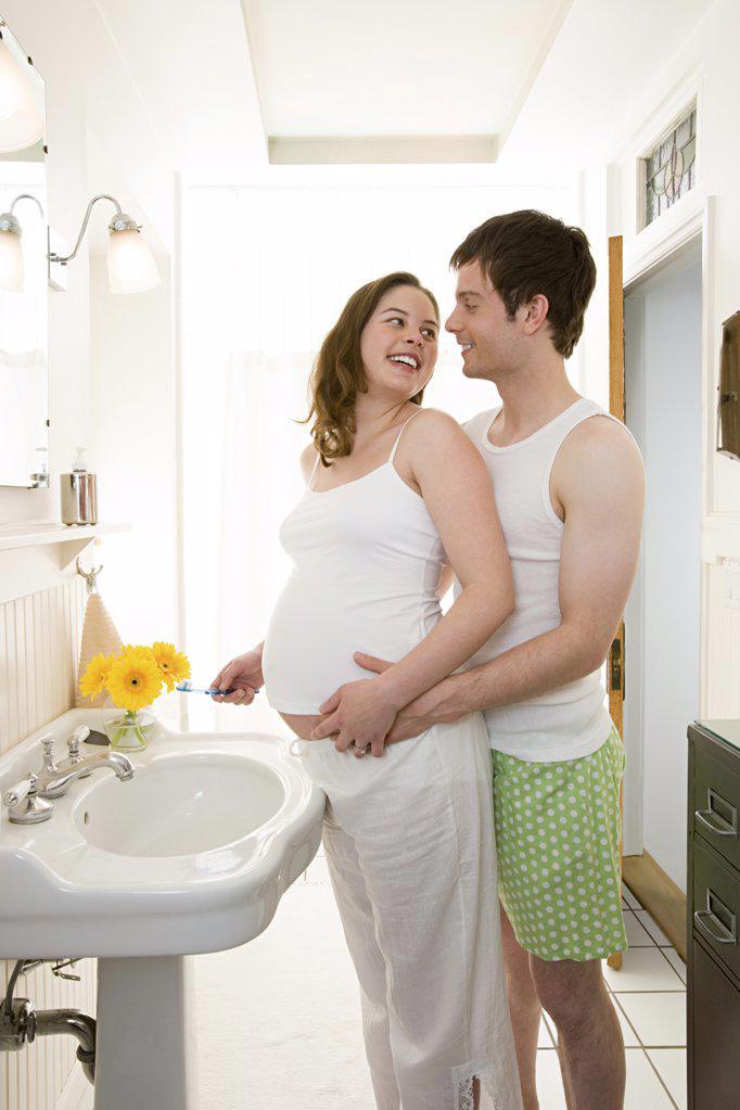Man hugging pregnant partner : Stock Photo