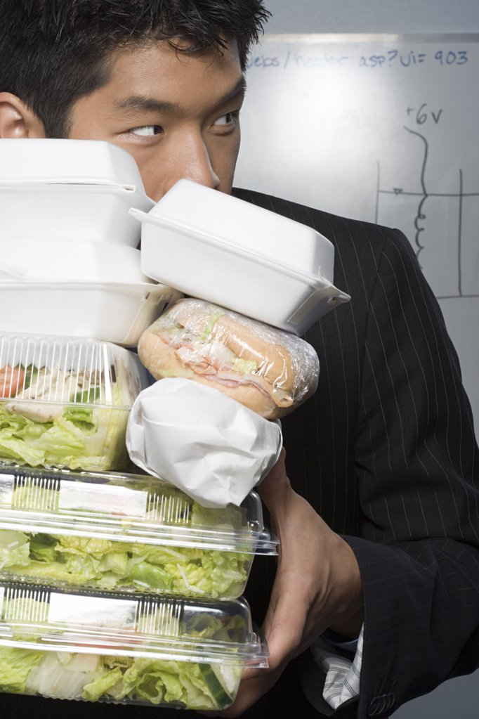 Stock Photo: 1439R-1018988 Businessman holding lots of food