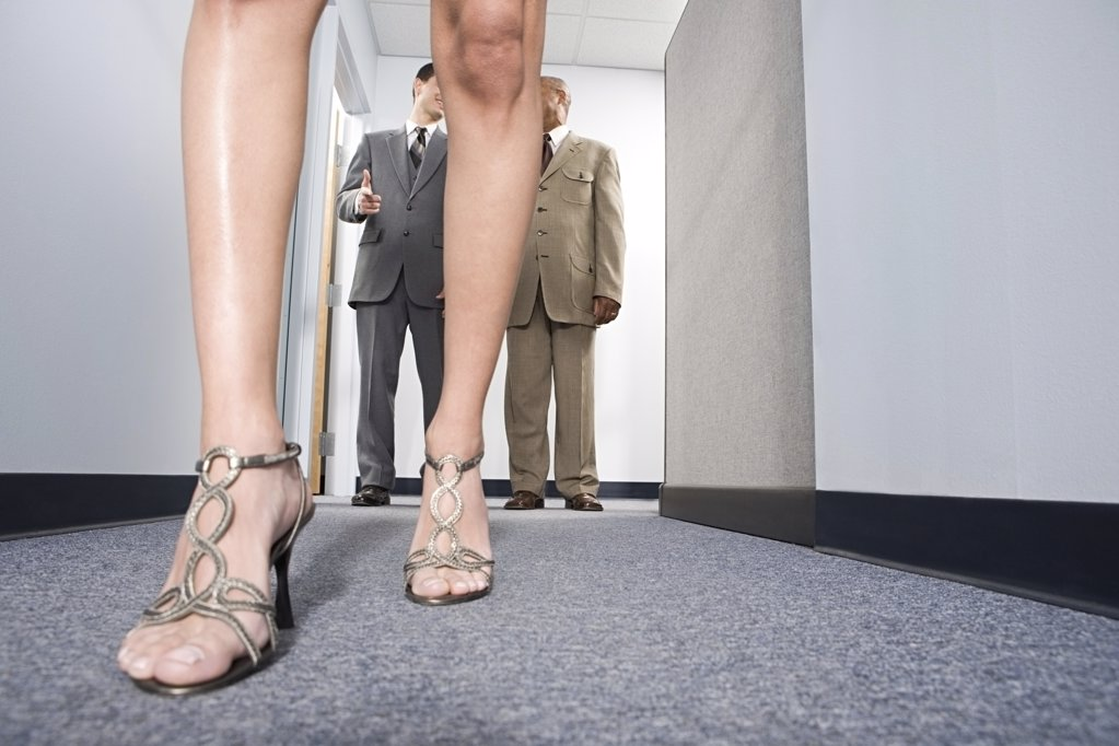 Businessmen looking at woman : Stock Photo