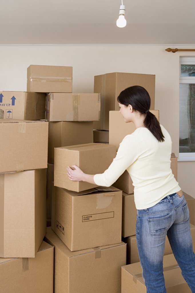 Stock Photo: 1439R-1019905 Woman stacking cardboard boxes