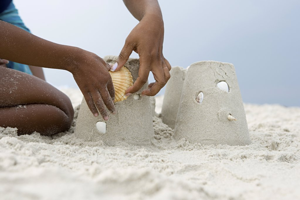 Stock Photo: 1439R-1025562 Mother and child putting a shell on a sandcastle
