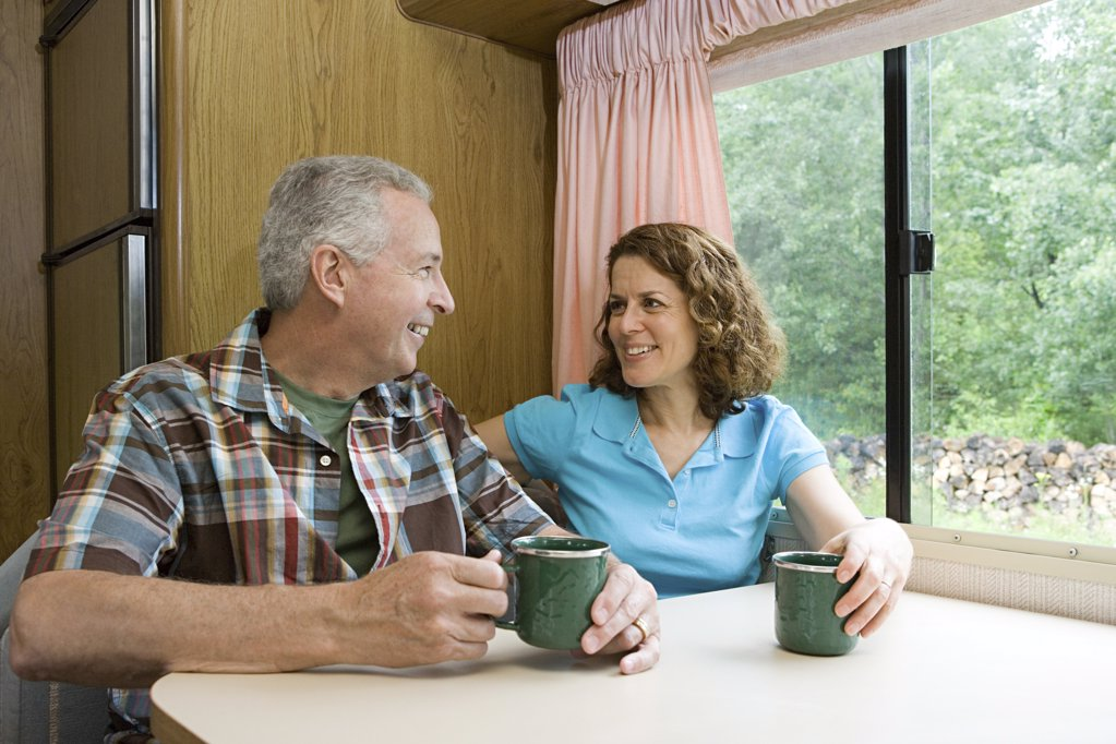 Stock Photo: 1439R-1027544 Couple drinking coffee in a caravan