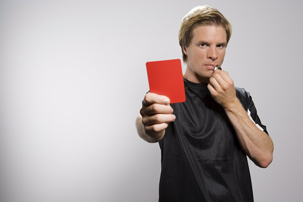 Referee holding red card and blowing whistle : Stock Photo