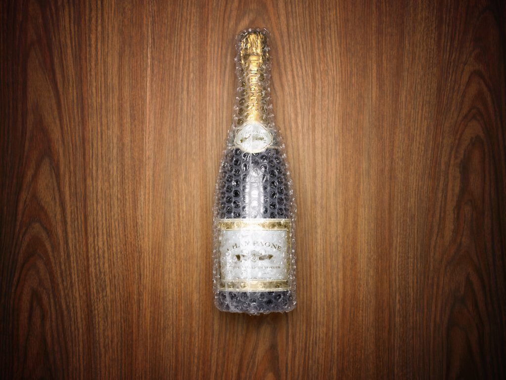 Champagne bottle wrapped in bubble wrap : Stock Photo