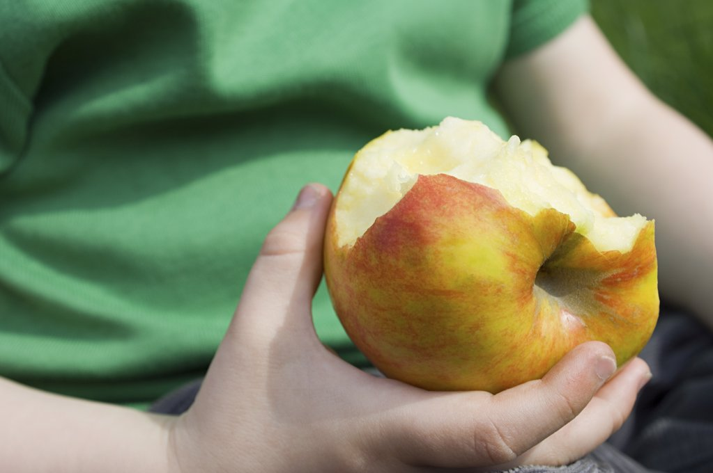 Child with an eaten apple : Stock Photo