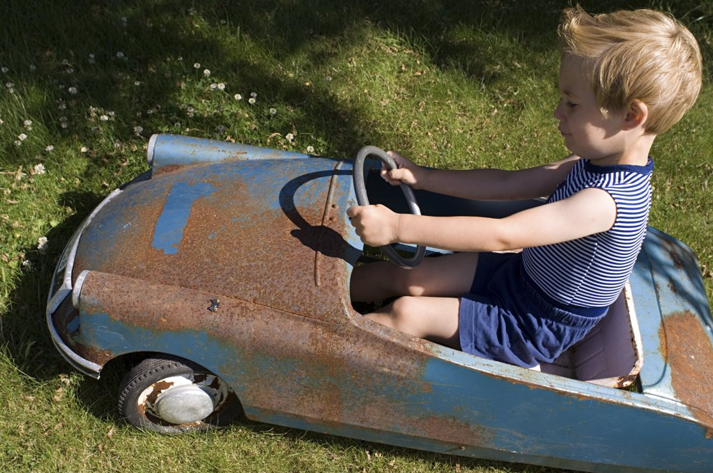 Boy in an old toy car : Stock Photo