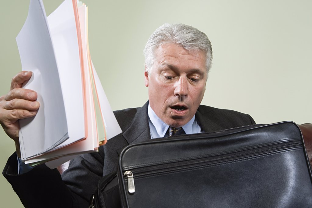 Panicked man looking in briefcase : Stock Photo