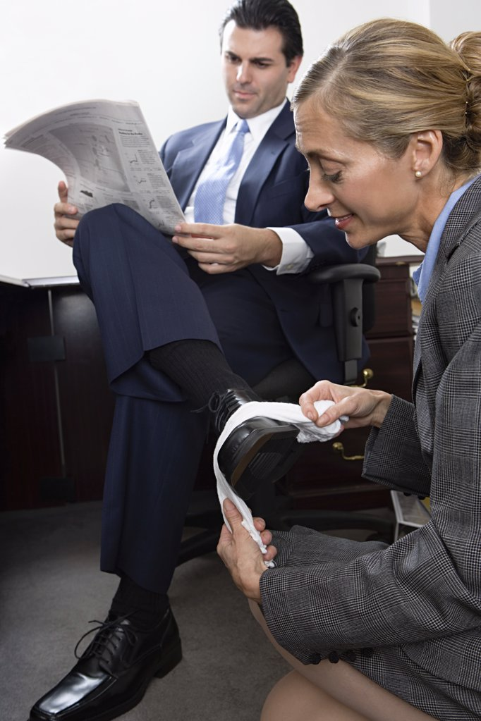 Woman polishing businessmans shoe : Stock Photo