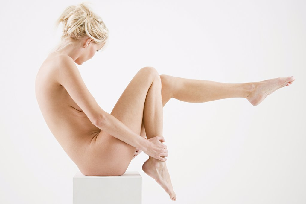 Nude woman sitting on a box : Stock Photo