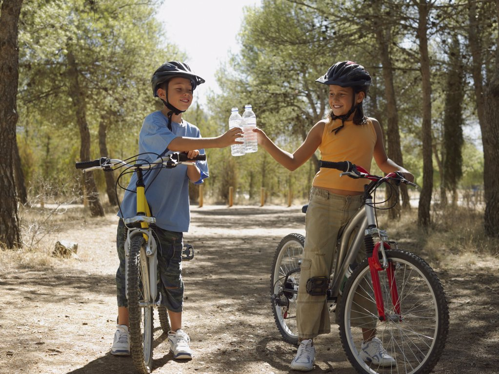 Stock Photo: 1439R-1032653 Boy and girl on bikes with water bottles