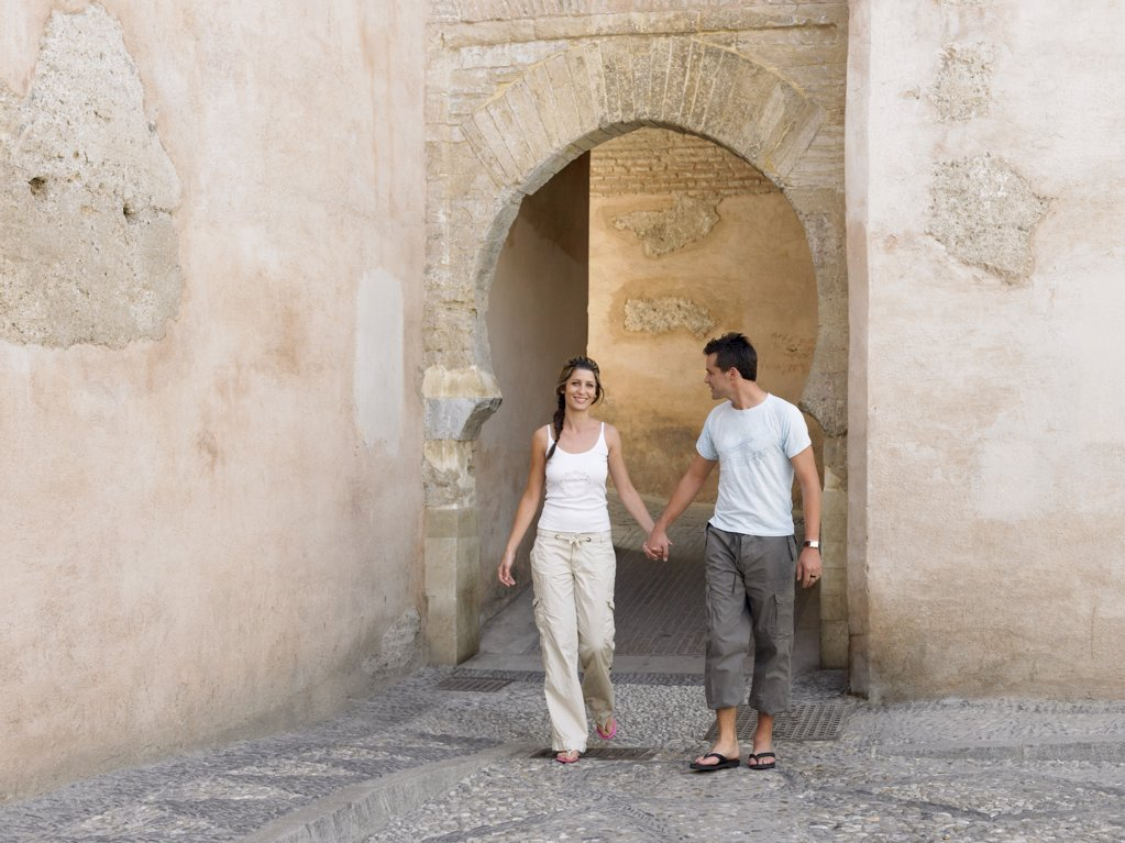 Couple hand in hand by arch : Stock Photo