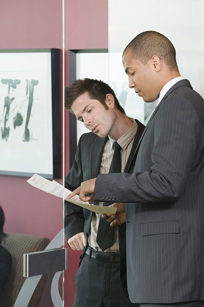 Two businessmen looking at paperwork : Stock Photo
