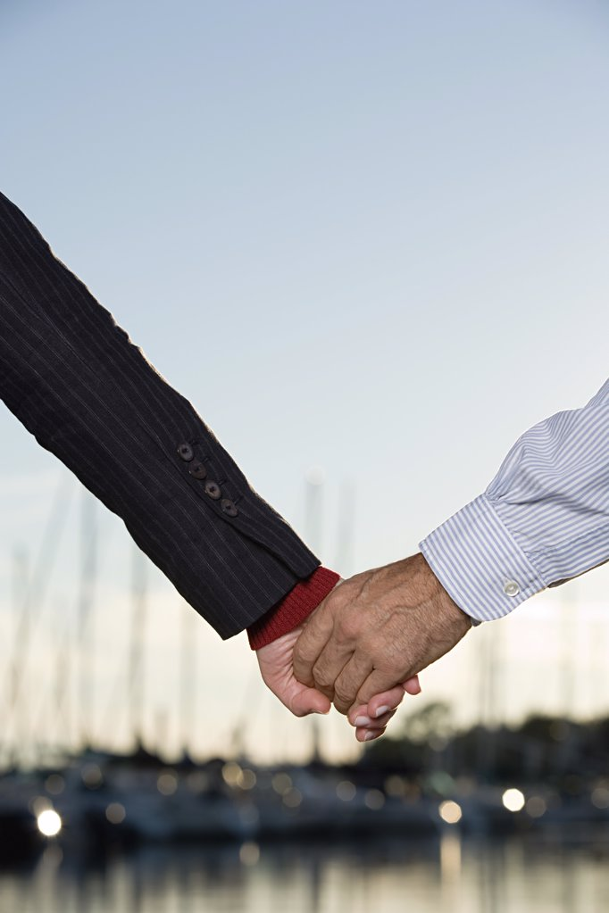 Couple holding hands at harbour : Stock Photo