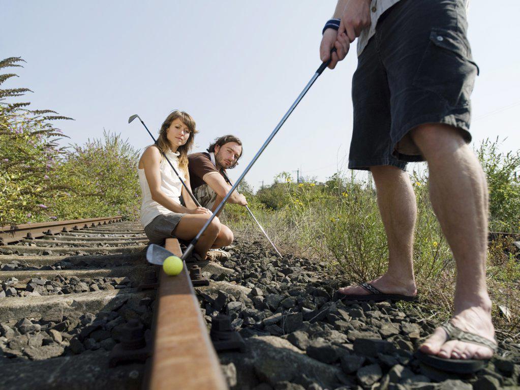 Stock Photo: 1439R-1034805 Golfers on railway tracks