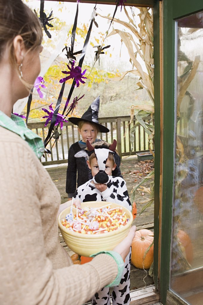 Stock Photo: 1439R-1035163 Woman with sweets for trick or treaters