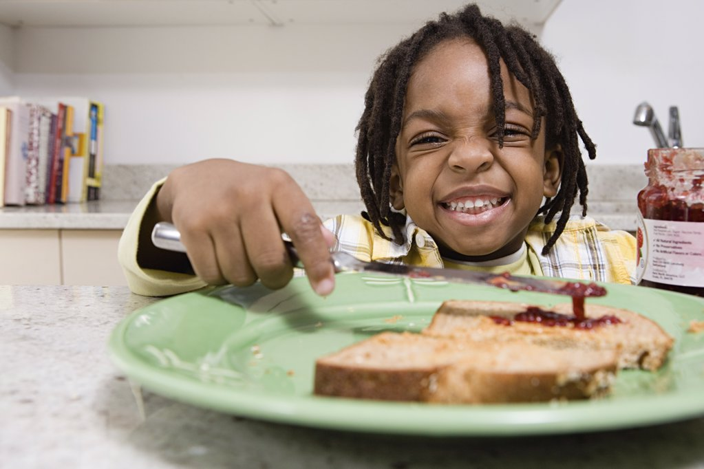 Boy spreading jam on toast : Stock Photo