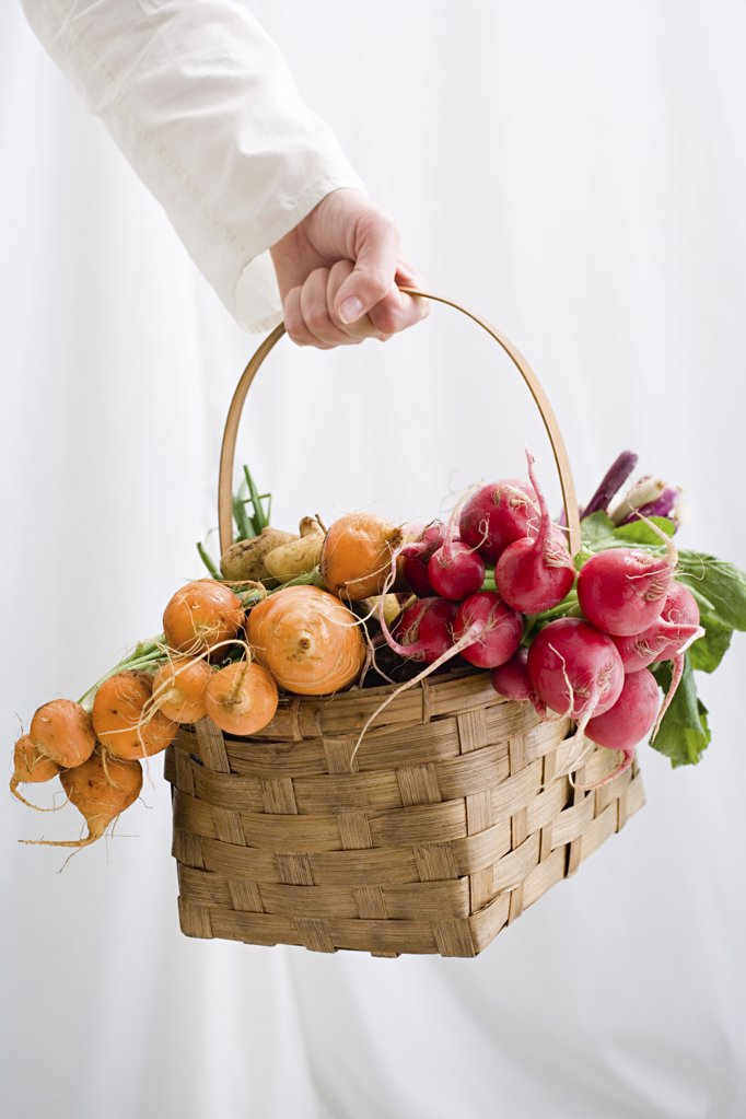 Woman holding basket of beetroot and radishes : Stock Photo