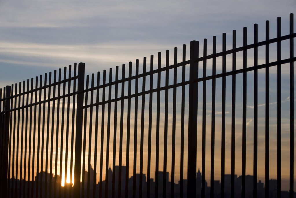 Stock Photo: 1439R-1060574 New york skyline through a fence