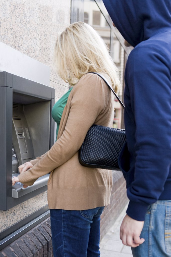 Thief looking over womans shoulder at cash machine : Stock Photo
