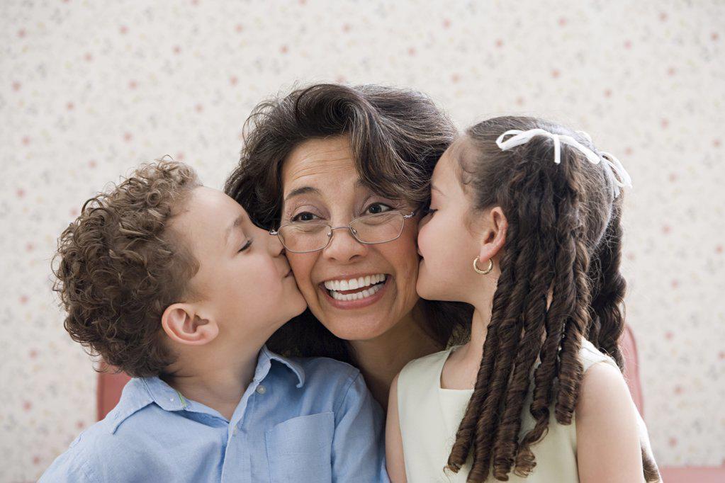 Stock Photo: 1439R-1076398 Kids kissing grandmother