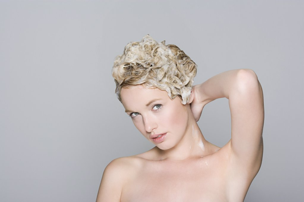 Portrait of a woman with shampoo in her hair : Stock Photo