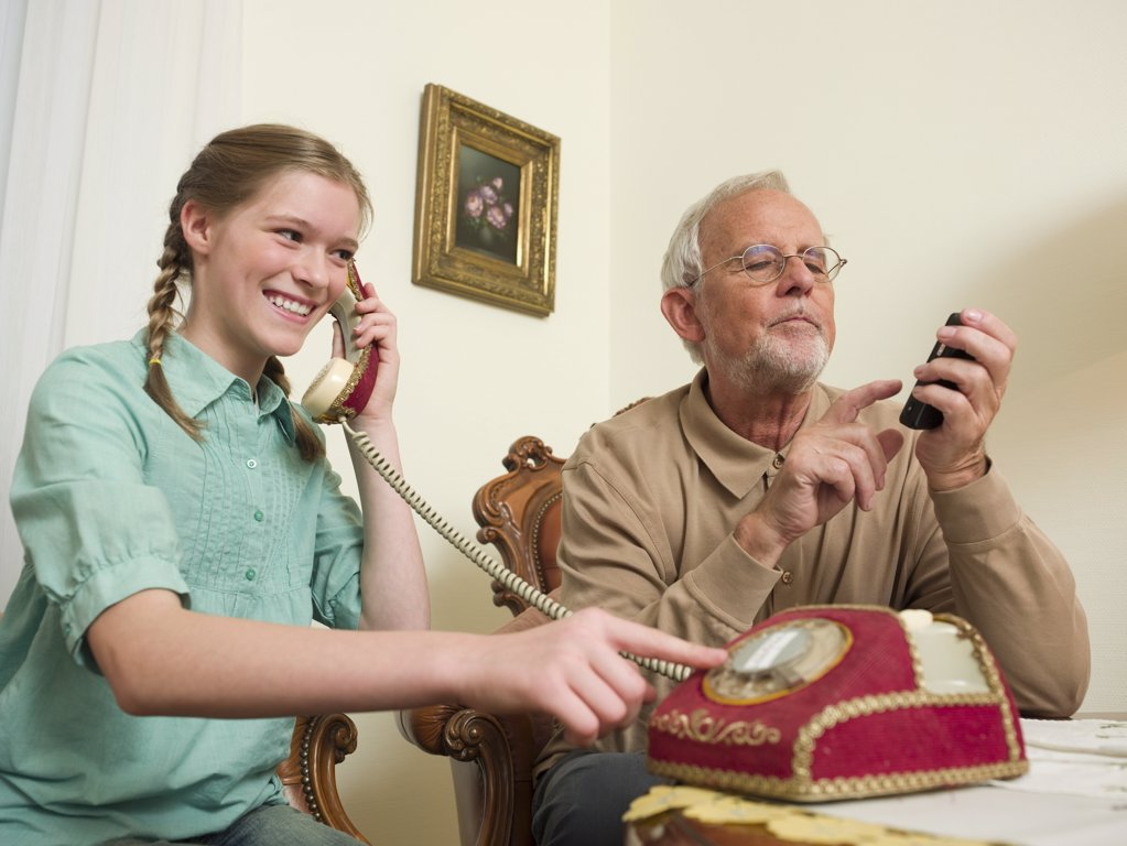 Grandfather and granddaughter using telephones : Stock Photo