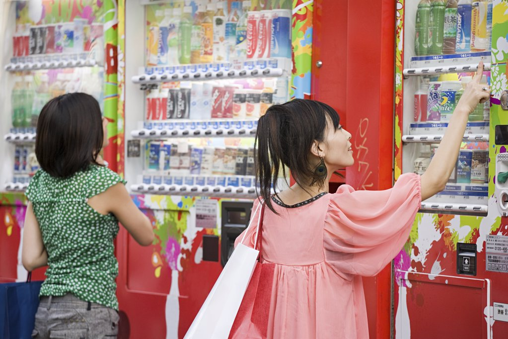Young women choosing drinks from a vending machine : Stock Photo