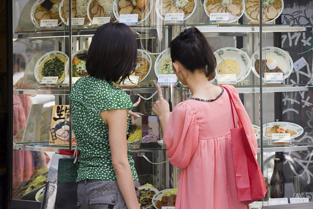 Stock Photo: 1439R-1082814 Friends looking in a restaurant window