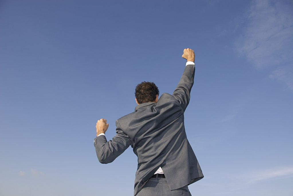 Rear view of a businessman with his arms raised : Stock Photo
