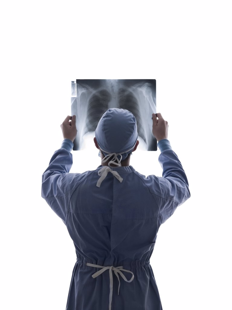 Stock Photo: 1439R-1090097 Surgeon looking at x-ray